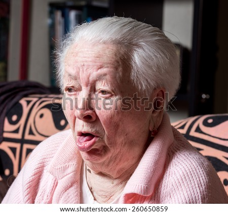 Old woman coughing at home - stock photo