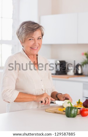 Old woman cutting vegetables on a cutting board with a smile in kitchen - stock photo