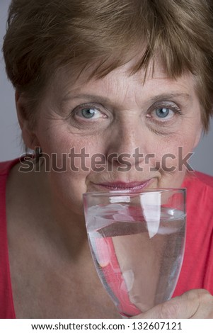 old woman drinking mineral water - stock photo