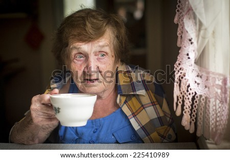 Old woman drinking tea at the window in his house.  - stock photo
