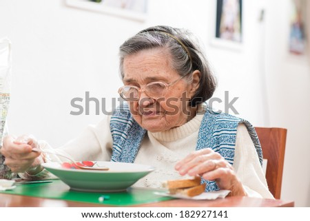 Old woman eating her lunch at home  - stock photo