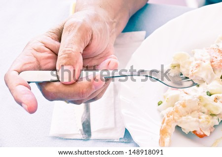 old woman eating russian salad - stock photo