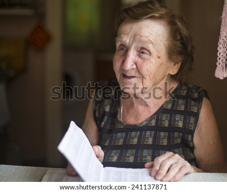 Old woman emotionally talks and reads in a notebook in his house. - stock photo