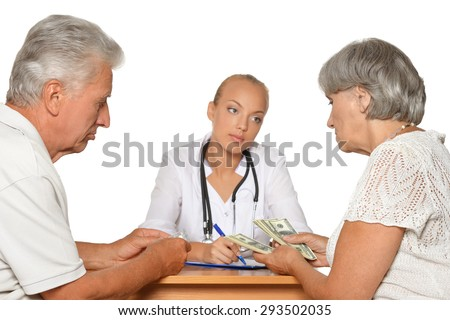 Old Woman giving money to female doctor on white - stock photo