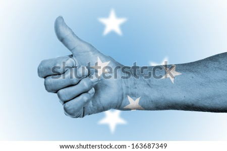 Old woman giving the thumbs up sign, isolated, flag of Micronesia