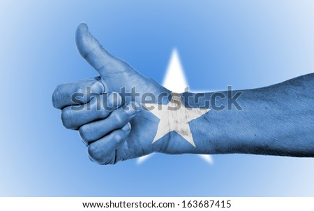 Old woman giving the thumbs up sign, isolated, flag of Somalia