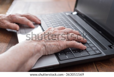 Old woman hands typing on a laptop keyboard