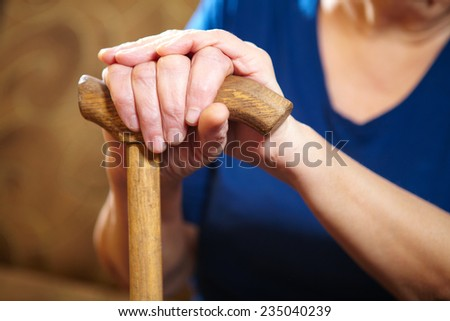 Old woman hands with cane. Senior people health care. - stock photo