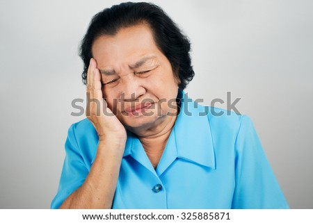 Old woman have a headache - stock photo