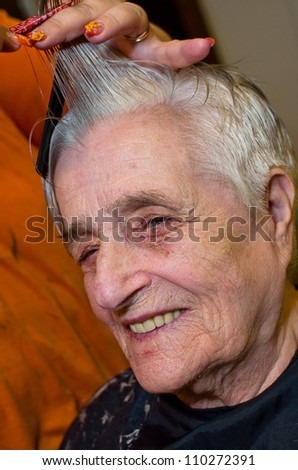 Old woman having a hair cut - stock photo