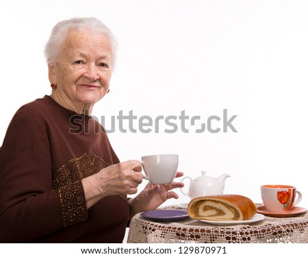 Old woman having breakfast on a white background - stock photo