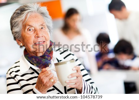 Old woman holding a cup of tea and smiling - stock photo