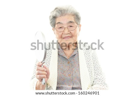 Old woman holding a hand mirror