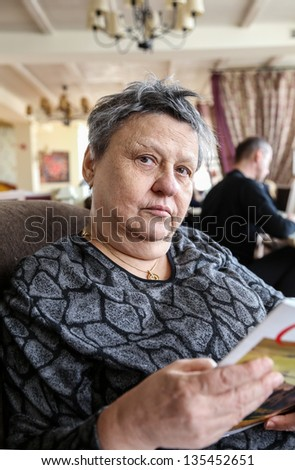 old woman holding a magazine - stock photo