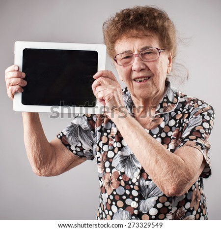 Old woman holding a tablet in the hands of. Seniors with tablen pc - stock photo