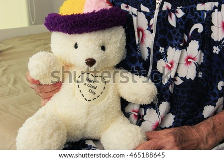 Old woman holding bear doll, have a good day