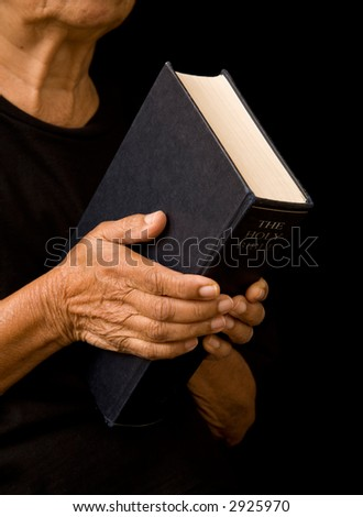 Old woman holding bible - stock photo