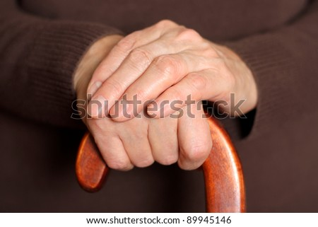 Old woman holding walking stick - stock photo