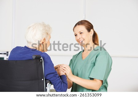 Old woman in a wheelchair as patient with geriatric nurse in a nursing home - stock photo