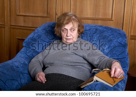 old woman in an armchair  glasses and with the book