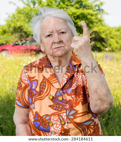 Old woman in angry gesture protecting her garden - stock photo