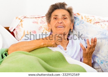 Old woman in bed talking and gesturing. - stock photo