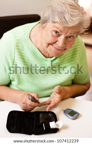old woman in blood sugar measure - stock photo