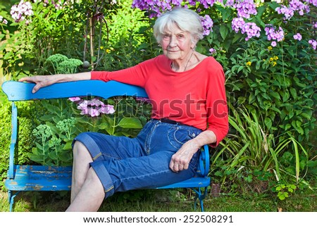 Old Woman in Casual Clothing Sitting on the Blue Wooden Bench at the Garden Looking at the Camera. - stock photo