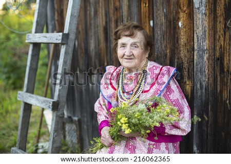 Old woman in ethnic clothes with wild flowers in their hands in the yard of his rural home. - stock photo