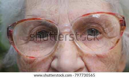 Old woman in eyeglasses looking into camera. Eyes of an elderly lady with wrinkles around them. Close up portrait of grandmother. Slow motion.
