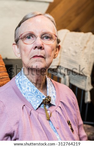 Old woman in pink sweater sitting straight and stern - stock photo