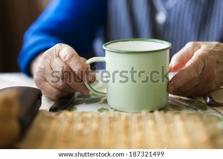 Old woman is drinking tea in her country style kitchen - stock photo