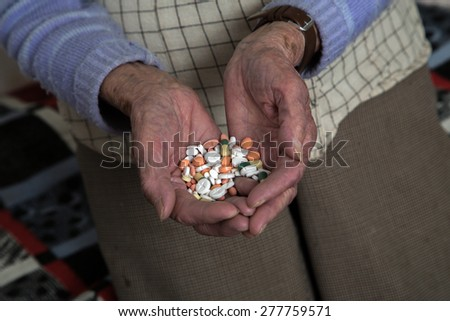 Old woman is holding medications in her hands - stock photo