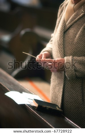 Old woman is reading a Holy Bible in a church and praying. - stock photo