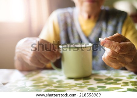 Old woman is taking pills in her country style kitchen - stock photo