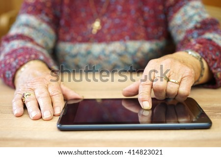 old woman is using tablet computer to surf on internet - stock photo