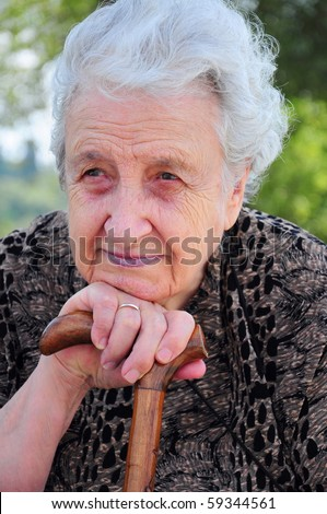 old woman leaning on her stick / cane - stock photo