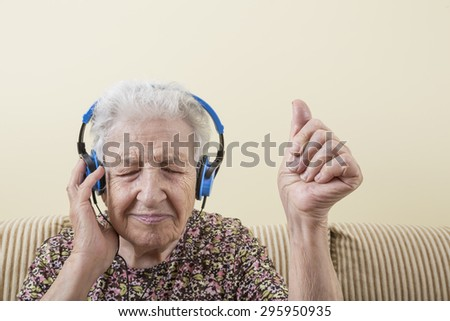 old woman listening music - stock photo