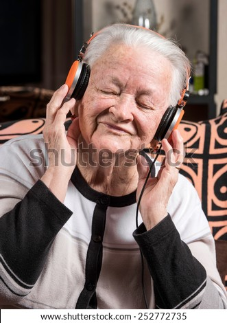 Old woman listening to music in headphones at home - stock photo