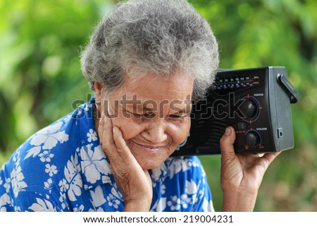 Old Woman Listening To Music With A Vintage Radio, outdoor - stock photo