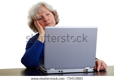 Old woman looking bored at her laptop - stock photo