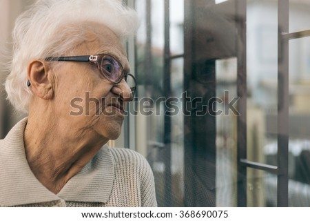 Old woman looking out the window. Concept about aging and loneliness - stock photo