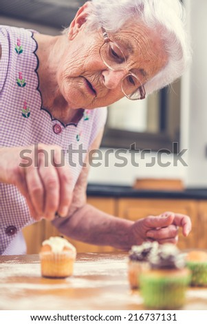 Woman Decorating Cupcakes old woman making decorating cupcakes stock photo 215748847