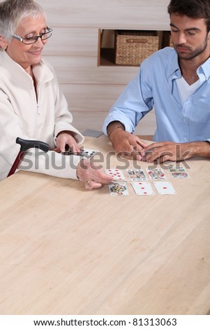 old woman playing cards with young man - stock photo