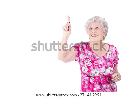 Old woman pointing up with her finger against a white background - stock photo