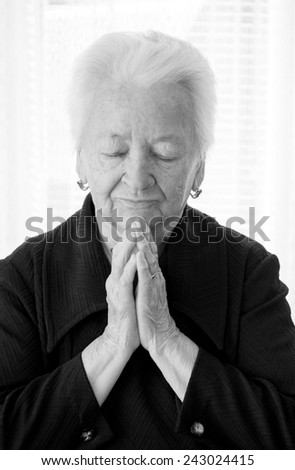 Old woman praying on a white background