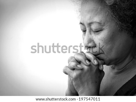 Old woman praying on white background - stock photo