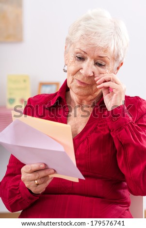 Old woman reading letter from her granddaughter and crying