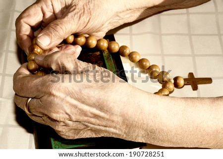 Old woman's hands holding rosary - stock photo