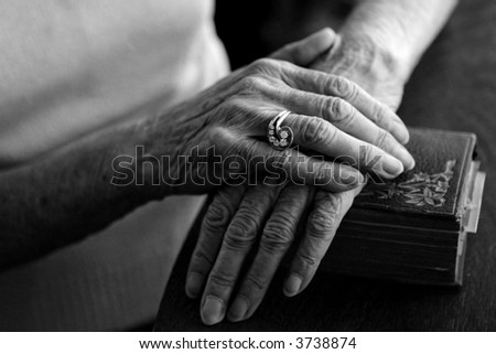 Old Woman's Hands on Her Bible Wearing Her Vintage Ring - stock photo